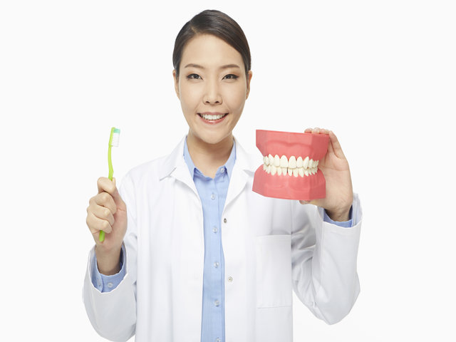 Medical personnel holding up a tooth brush and a set of dentures